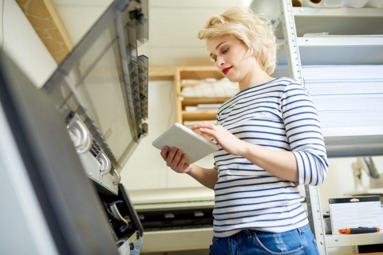 Kobieta steruje pracą drukarki za pomocą tabletu